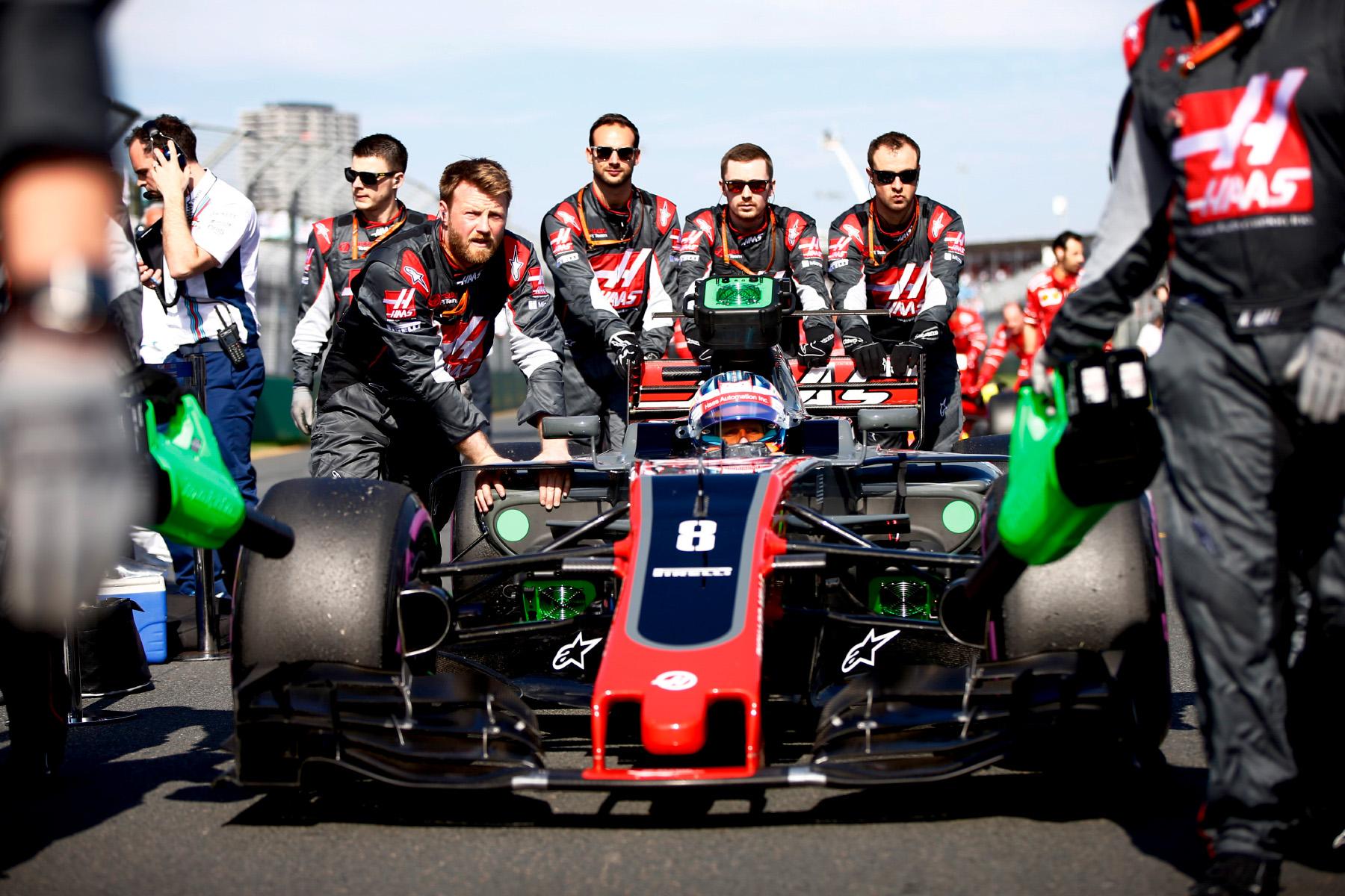 Romain Grosjean is wheeled in his car to the grid.