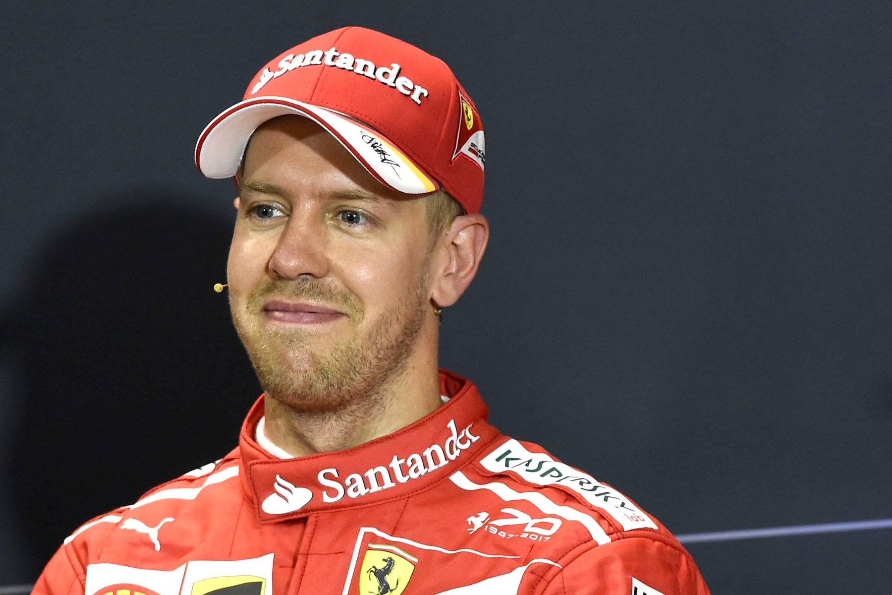 Sebastian Vettel grins in a press conference.