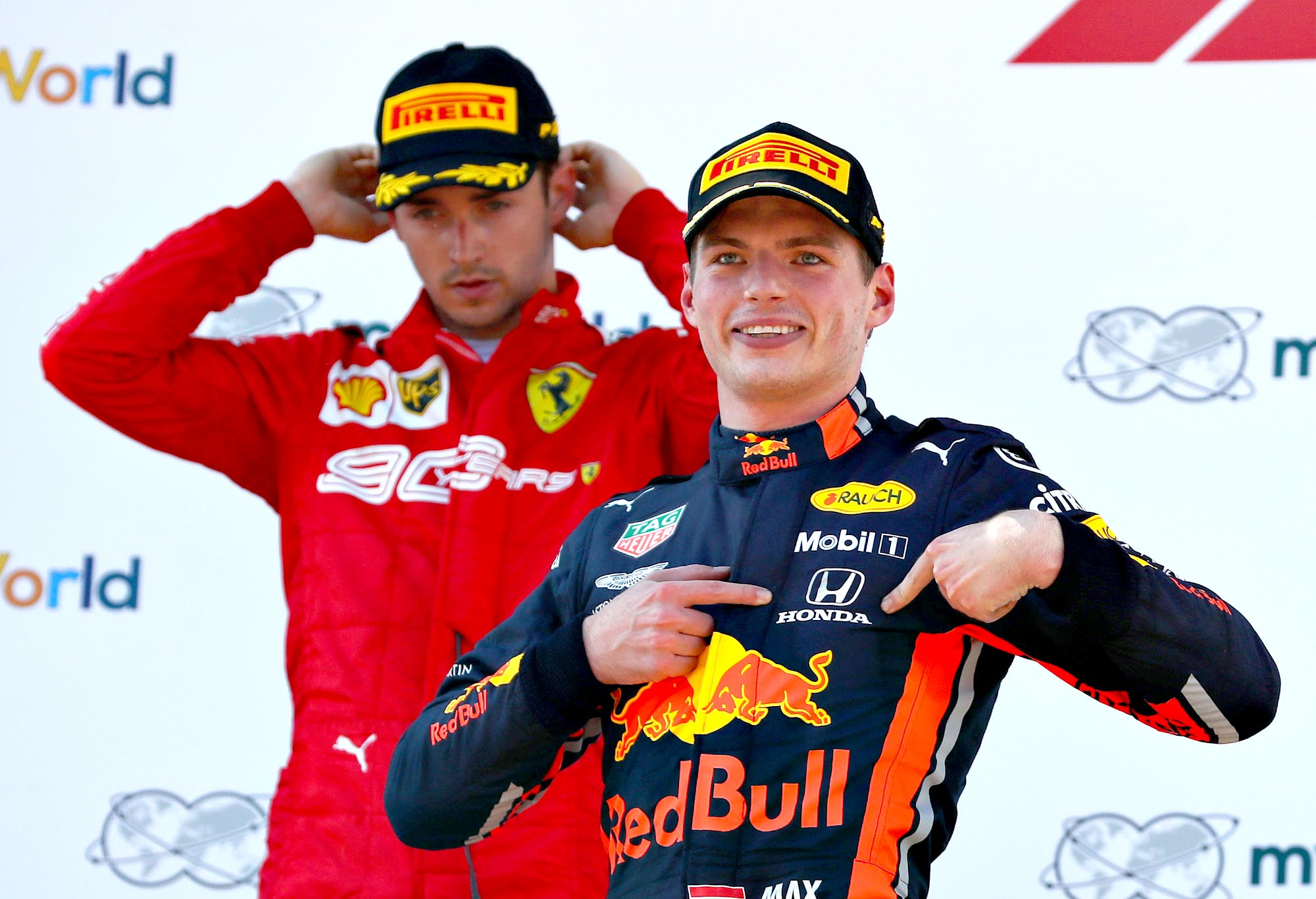 Max Verstappen points to the Honda logo on his overalls from the Austrian GP podium.